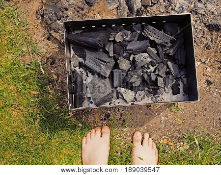 Close up of barbecue grill mangal in preparation, coal without fire on green grass