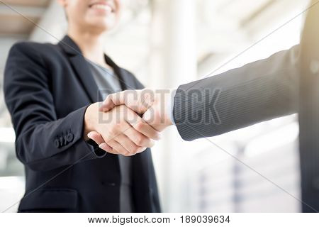 Businesswoman making handshake with a businessman -greeting dealing merger and acquisition concepts