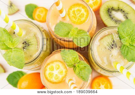Freshly blended orange kumquat and green kiwi fruit smoothie in glass jars with straw mint leaf cut ripe berry top view close up. White wooden board background.