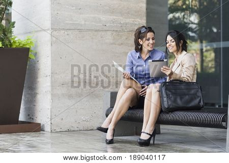Hispanic businesswomen sitting on bench looking at digital tablet