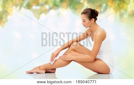 people, beauty and hair removal concept - beautiful woman with epilator removing hair from legs sitting on floor over natural green background and lights