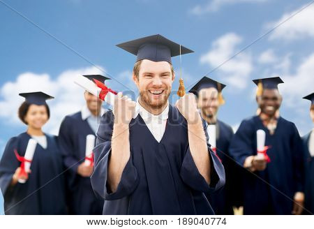 education, gesture and people concept - group of happy international students in mortar boards and bachelor gowns with diplomas celebrating successful graduation over blue sky and clouds background