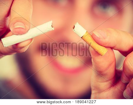 Smilling Man Is Breaking A Cigarette