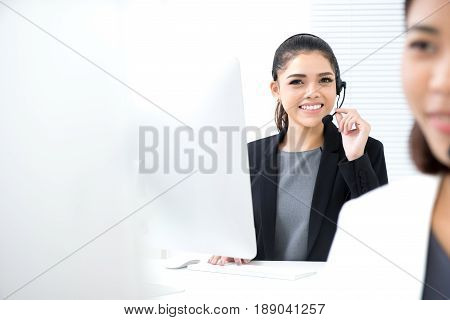 Young Asian businesswoman working as an operator (or telemarketer) in call center