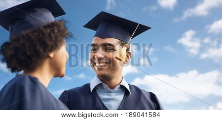 education, graduation and people concept - happy international students in mortar boards and bachelor gowns over blue sky and clouds background