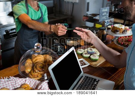 Staff giving credit card to customer at counter in coffee shop