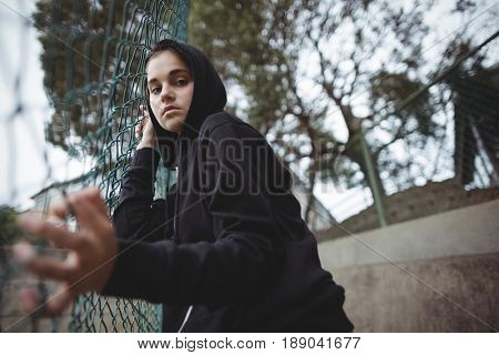 Portrait of anxious teenage girl leaning on wire mesh fence at school campus