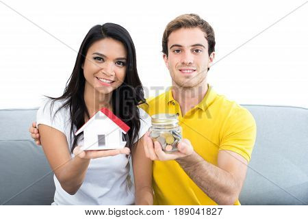 Young interracial couple on the couch showing money and house model - financial planning saving and real estate buying concepts