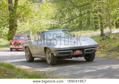 STOCKHOLM SWEDEN - MAY 22 2017: Silver Chevrolet Corvette classic car from 1964 driving on a country road in the public race Gardesloppet in the forests at Djurgarden Stockholm Sweden. May 22 2017