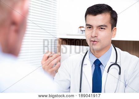 Doctor talking with senior male patient - medical consultation and examination concepts