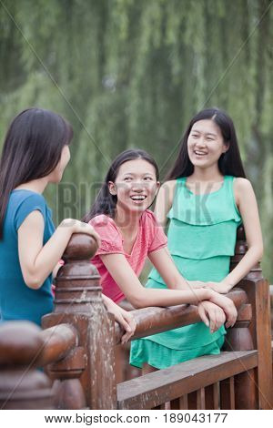 Chinese women leaning on wooden railing