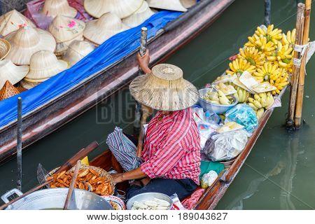 Local vendors selling goods at Damnoen Saduak Floating Market near Bangkok in Thailand Damnoen Saduak is a very popular tourist attraction.