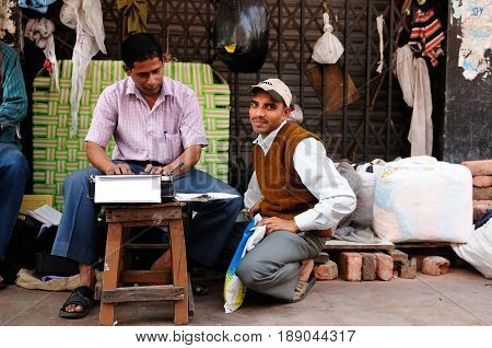 CALCUTTA INDIA - 07 DECEMBER 2009: Man dealing with professionally applying on a typewriter in streets of Indian cities