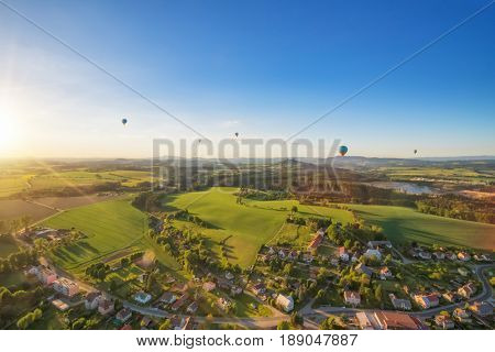 Group of hot air balloons flying above rural countryside of Czech republic, Europe. Air travel and transportation, beautiful nature landscape shot from aerial perspective