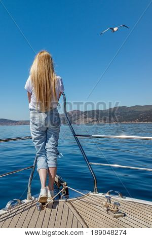 A girl on a yacht looks at the blue sea. A clear summer day. Seagull in the blue sky. Balaclava Bay - the Black Sea resort