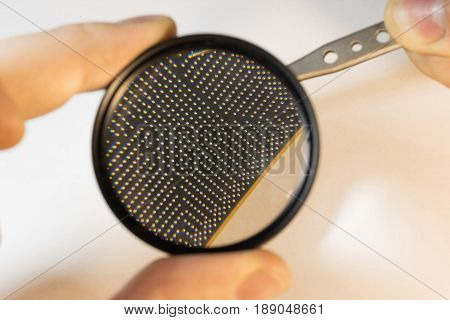 inspection the contacts of a bga chip under a magnifying glass keep the chip tweezers
