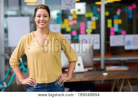 Portrait of smiling female executive standing with hands on hip at office