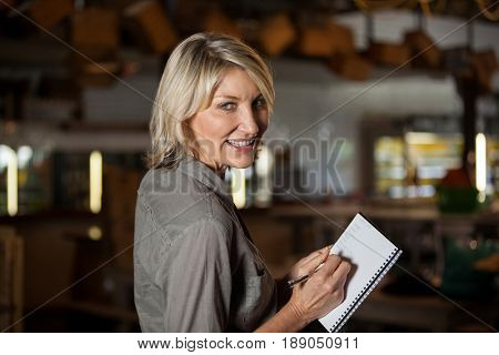 Portrait of female costumer maintain record in notepad at supermarket