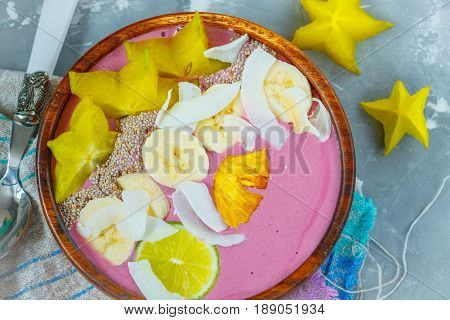 Pink tropical smoothie bowl (carambola pineapple coconut). Love for a healthy vegan food concept