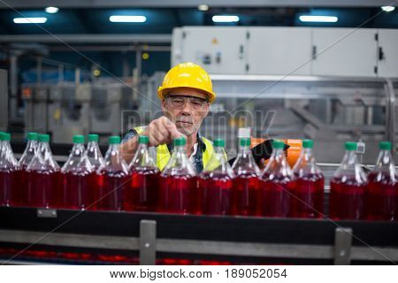 Male factory worker monitoring cold drink bottles at drinks production factory