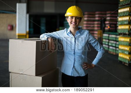 Portrait of smiling female factory worker standing with hand on hip in factory