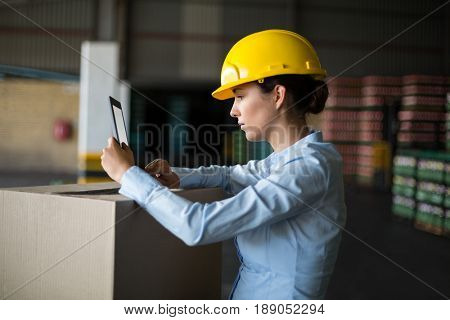 Attentive female factory worker using digital tablet in factory