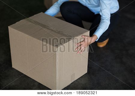 Female factory worker picking up cardboard boxes in factory