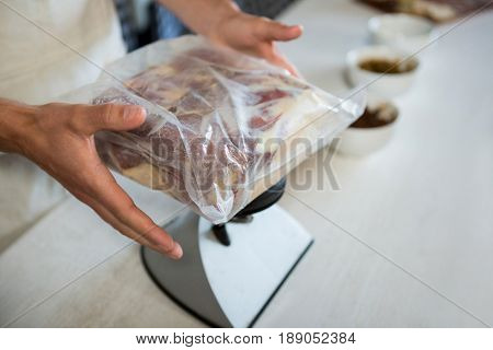 Staff checking the weight of meat packet at counter in market
