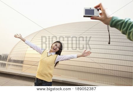 Chinese man taking photograph of girlfriend