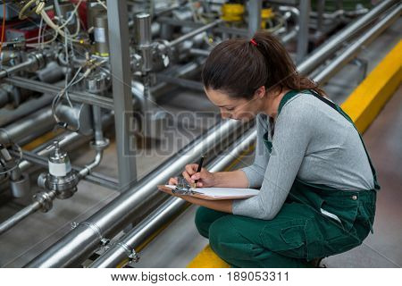Female factory worker maintaining record on clipboard in drinks production factory