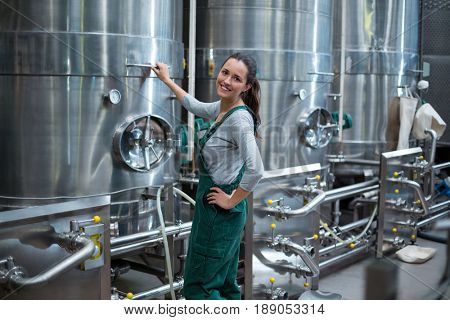 Portrait of female factory worker standing near control wheel of storage tank at drinks production factory