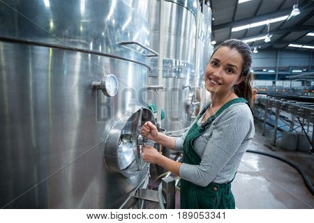 Portrait of female factory worker turning control wheel of storage tank at drinks production factory