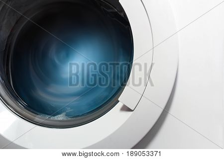 Front view and portion of the porthole of the washing machine during washing and rotation of the drum containing clothes blue