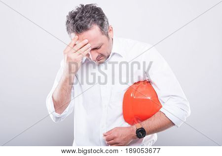 Portrait Of Architect Holding Hardhat Making Tired Gesture