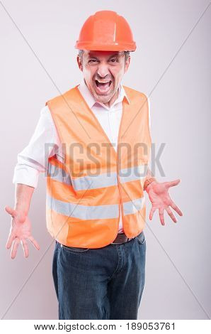 Foreman Wearing Reflective Vest And Hardhat Screaming