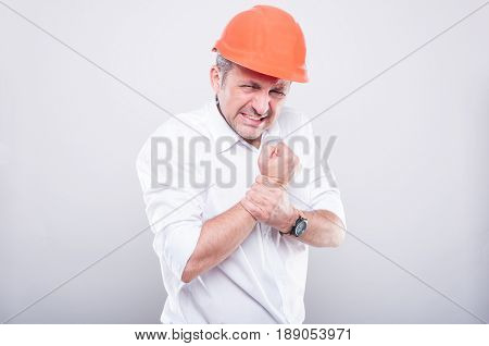 Portrait Of Contractor Wearing Hardhat Holding Wrist Like Hurting