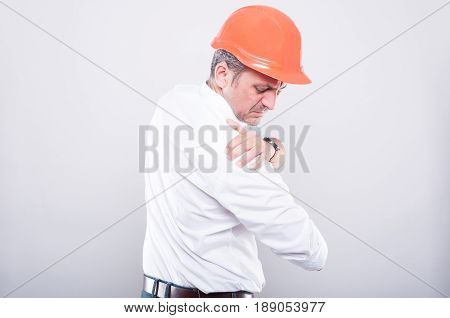 Side View Of Architect Wearing Hardhat Holding Shoulder Like Hurting