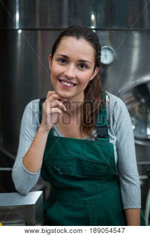 Portrait of female factory worker standing with arms crossed at drinks production factory