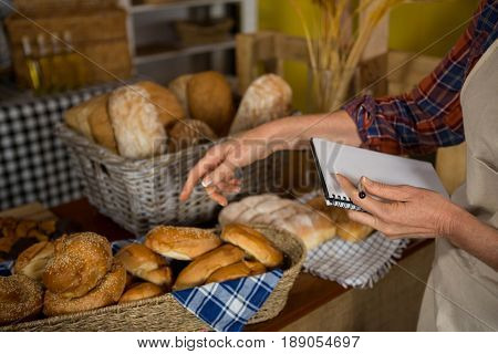 Female staff maintaining stock record at bread counter in bakery shop