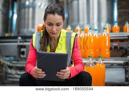 Female factory worker using digital tablet at drinks production factory