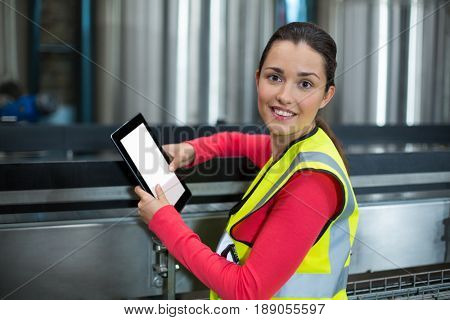 Portrait of female factory worker using digital tablet at drinks production factory