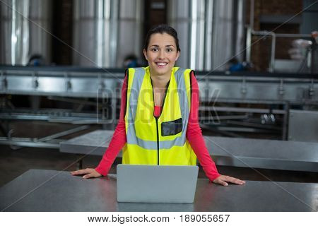 Portrait of smiling factory worker standing in drinks production factory