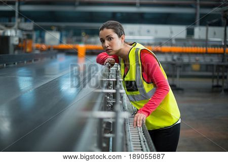 Female factory worker checking conveyor belt at drinks production factory