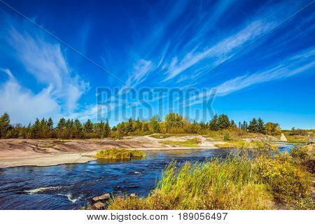 Incredible cirrus clouds over the Winnipeg River. Indian summer. Old Pinawa Dam Park. The concept of ecological and recreational tourism