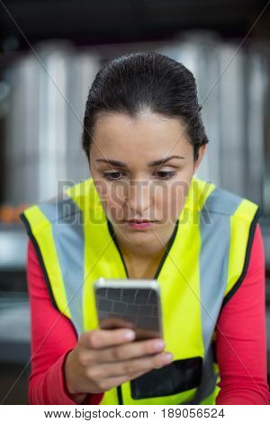 Female factory worker using mobile phone at drinks production factory