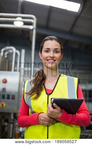 Portrait of female factory worker holding digital tablet at drinks production factory