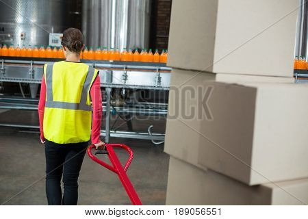 Rear view of female factory worker pulling trolley of cardboard boxes at drinks production factory