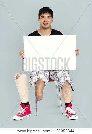 Disability Young Man with Prosthesis Leg Holding Blank Paper Board Studio Portrait
