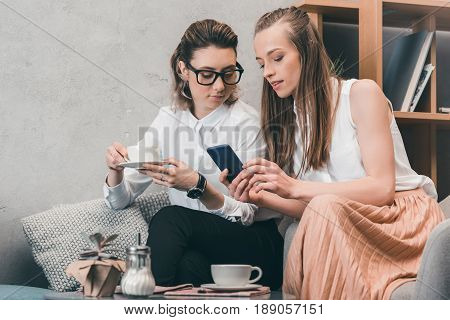Beautiful Happy Homosexual Couple Using Smartphone And Drinking Coffee In Cafe