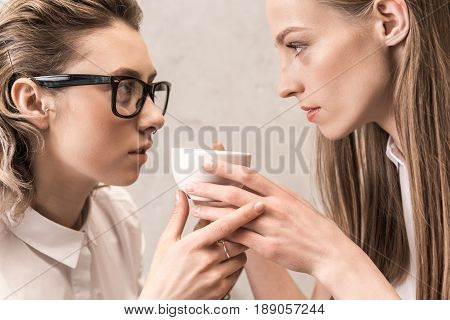 Side View Of Beautiful Young Women Holding Coffee Cup And Looking At Each Other